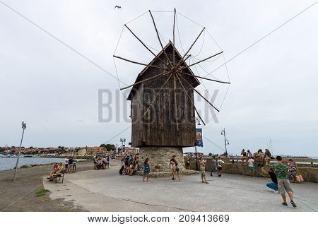 NESEBAR BULGARIA - AUGUST 21 2017: An old wooden windmill on the embankment in the old town. Nesebar is an ancient city and one of the major seaside resorts on the Bulgarian Black Sea Coast.