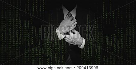 Businessman in black suit with abstract green computer code graphic background