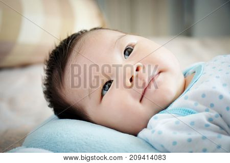 Asian baby portrait. cute Asian baby girl open eyes on the comfortable bed looking for parent on day time with little smile. happy children concept.