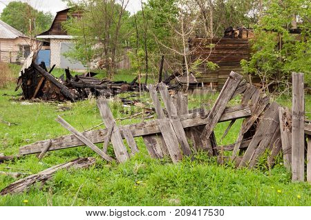 a broken fence behind which are the remains of a burned wooden house