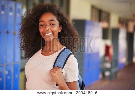 Happy black teenage girl smiling in high school corridor