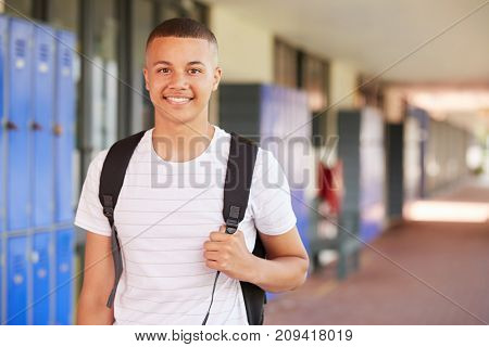Happy mixed race teenage boy smiling in high school corridor