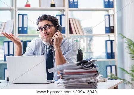 Young businessman under pressure in office to deliver tasks
