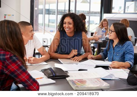 Teacher studying school books in class with high school kids
