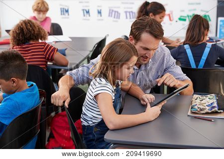 Teacher and schoolgirl using tablet computer in class