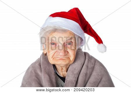 Elderly woman with Alzheimer disease holding a warm blanket and wearing Santa Claus cap on isolated