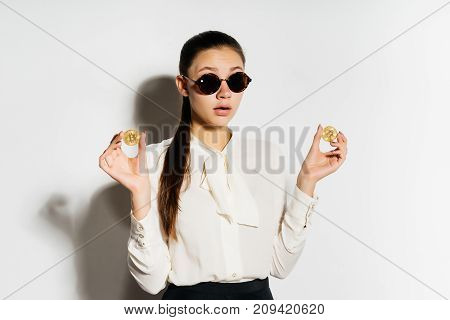 young surprised business lady in sunglasses holds gold bitcoins in hands