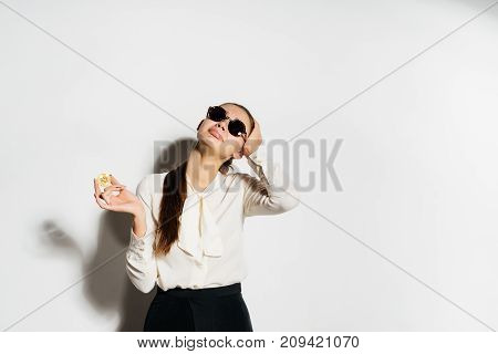 young business woman in sunglasses holds a gold bitcoin in her hand
