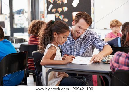 Teacher working with young schoolgirl at her desk in class