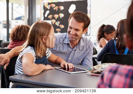 Teacher and schoolgirl using tablet looking at each other