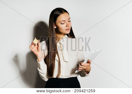 young smart modern business lady holding securities and gold bitcoin in her hands