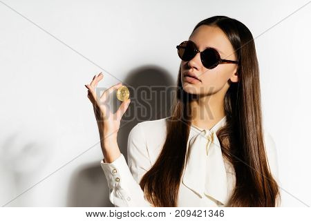 a dark-haired businesswoman in sunglasses is holding a gold bitcoin, a crypto currency