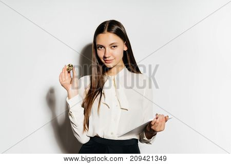 young smiling business lady holding a gold bitcoin and a tablet, studying crypto currency