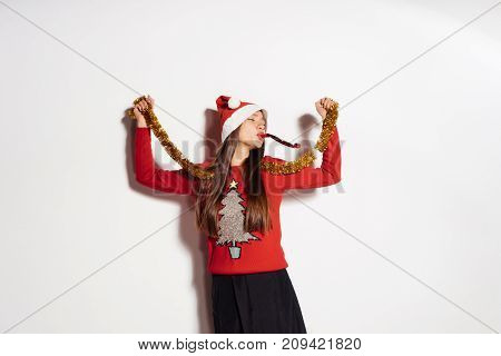happy girl in a red sweater with a Christmas tree, gold tinsel on her neck celebrates Christmas and a new year