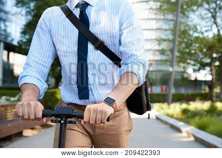 Close Up Of Businessman Commuting To Work On Scooter
