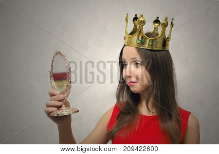 Young beautiful woman in red dress with golden crown above her head admires herself in the mirror. VIP client. Premium user concept. Success. Award ceremony. Beauty contest. First place in pageant.