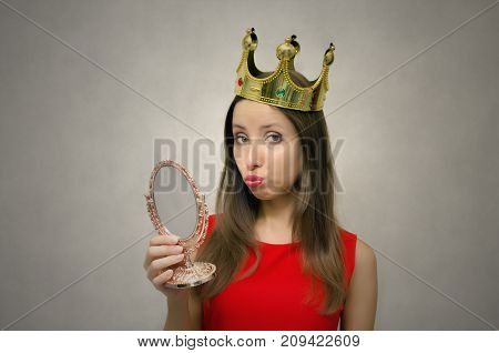 Young beautiful woman in red dress with golden crown above her head with mirror in hand. VIP client. Premium user concept. Success. Award ceremony. Beauty contest. First place in pageant.