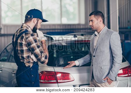 Side profile view of experienced brunet bearded expert specialist in cap and uniform and businessman in classy suit presenting his car broken demage discussing it diagnostic upgrading