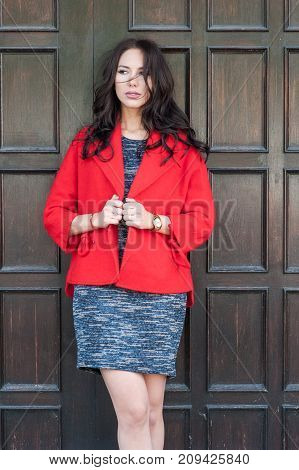 Young beautiful stylish woman dressed in a red coat gray knitted dress black boots against the background of a wooden door. Street style spring and autumn trend a flirty look.