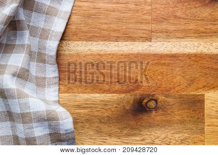 Checkered tablecloth over wooden table. Top view.