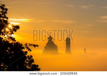 Landscape: Church silhouette floating in the clouds at dawn.