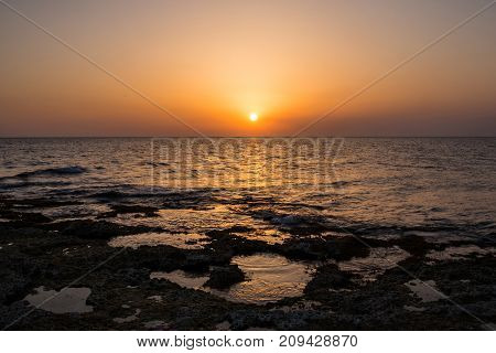 Landscape: Sunset over the sea. Waves and the Sun.