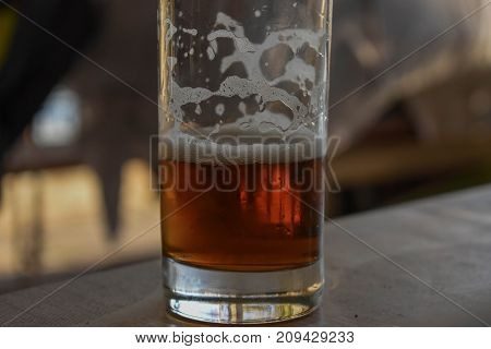 Craft beer. A half-drunk glass of beer at the table