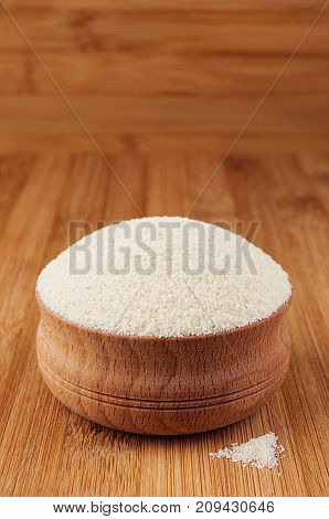 Semolina in wooden bowl on brown bamboo board closeup. Healthy dietary groats background.