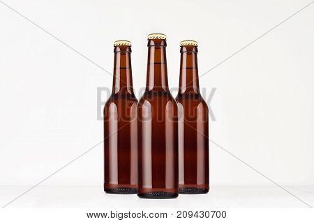 Group brown longneck beer bottle 330ml mock up. Template for advertising design branding identity on white wood table.