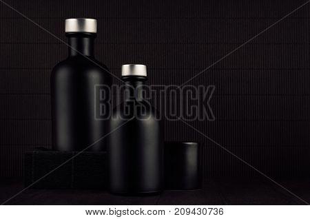 Dark black minimalist interior. Blank black cosmetics bottles on dark wood board mock up. Noir elegant home decor for advertising designers branding identity cover.