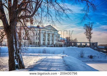 A beautiful building with columns on the banks of the Volga River next to the trees. Artistic noise is added to the photo. Mansion on the waterfront of Uglich, Russia.