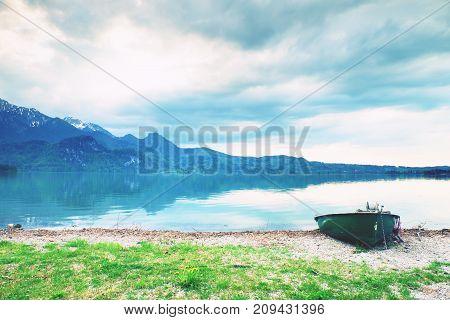 Abandoned Fishing Paddle Boat On Bank Of Alps Lake. Morning Lake Glowing By Sunlight.