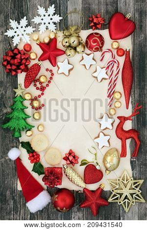 Abstract background of christmas  symbols with bauble decorations, mince pies, gingerbread cookies, candy canes and foil wrapped chocolates on parchment paper and rustic wood.