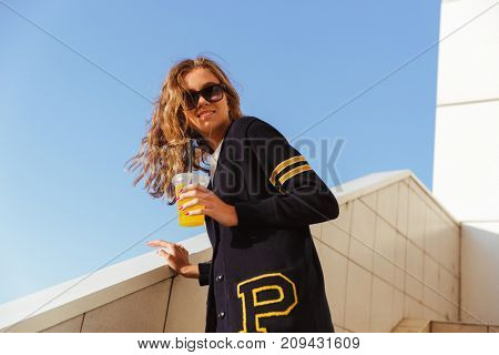 Smiling teenage girl in sunglasses drinking orange juice with a straw while standing on steps outdoors