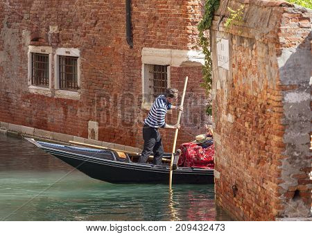 VENICE ITALY-SEPTEMBER 22 2017: Venetian gondolier rowing through the side narrow canal. Gondola is iconic traditional boat very popular means of transport for tourists