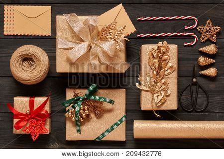 Creatively wrapped and decorated christmas presents in boxes on dark wooden background.Top view from above. Flat lay.
