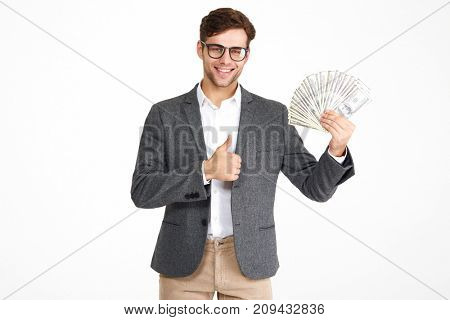 Portrait of happy satisfied man in eyeglasses and a jacket holding bunch of money banknotes while standing and showing thumbs up gesture isolated over white background