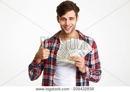 Portrait of a happy confident man holding bunch of money banknotes and showing thumbs up gesture isolated over white background