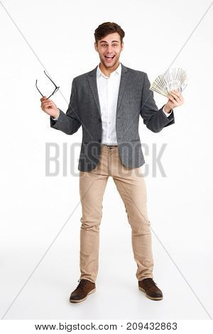 Full length portrait of happy excited man in a jacket holding bunch of money banknotes while standing and celebrating success isolated over white background