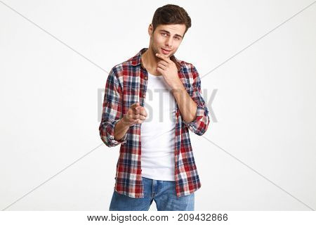 Portrait of a smiling charming man holding hand on his chin and pointing at camera isolated over white background