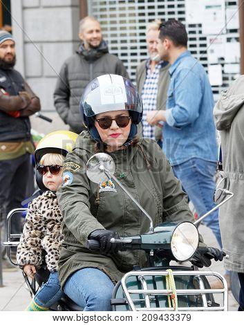 STOCKHOLM SWEDEN - SEPT 02 2017: Mother and child wearing old fashioned clothes driving vespa scooter at the Mods vs Rockers event at the Saint Eriks bridge Stockholm Sweden September 02 2017