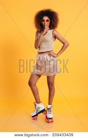 Full length portrait of a young afro american woman dressed in retro clothes and wearing skates while standing and showing silence gesture isolated over yellow background