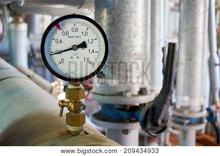 Manometer on the hot water pipeline in boiler.