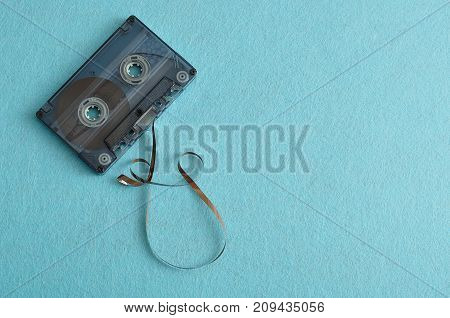 An old tape cassette isolated on a blue background