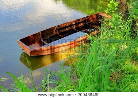 A red orange wooden boat sits on a lake filling with water