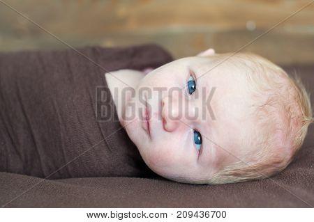 Temporary strabismus newborn baby with blue eyes