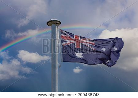 Australian Flag On A Flag Pole With Rainbow In The Sky. Patriotism Concept.