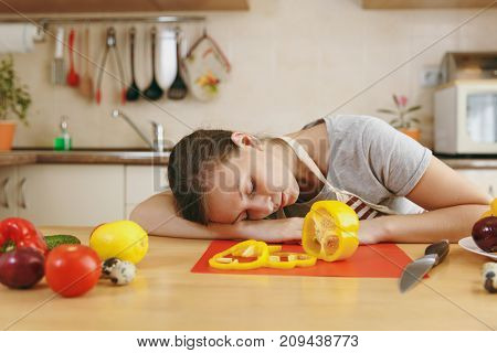 A Young Emaciated Tired Woman In An Apron Sleeping At The Table In The Kitchen At Home. Dieting Conc