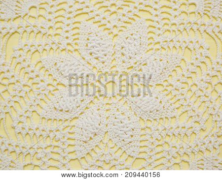 White handmade crochet lace doily on a yellow background