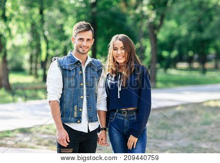 Pair Of Young People Standing In Park And Hold Hands